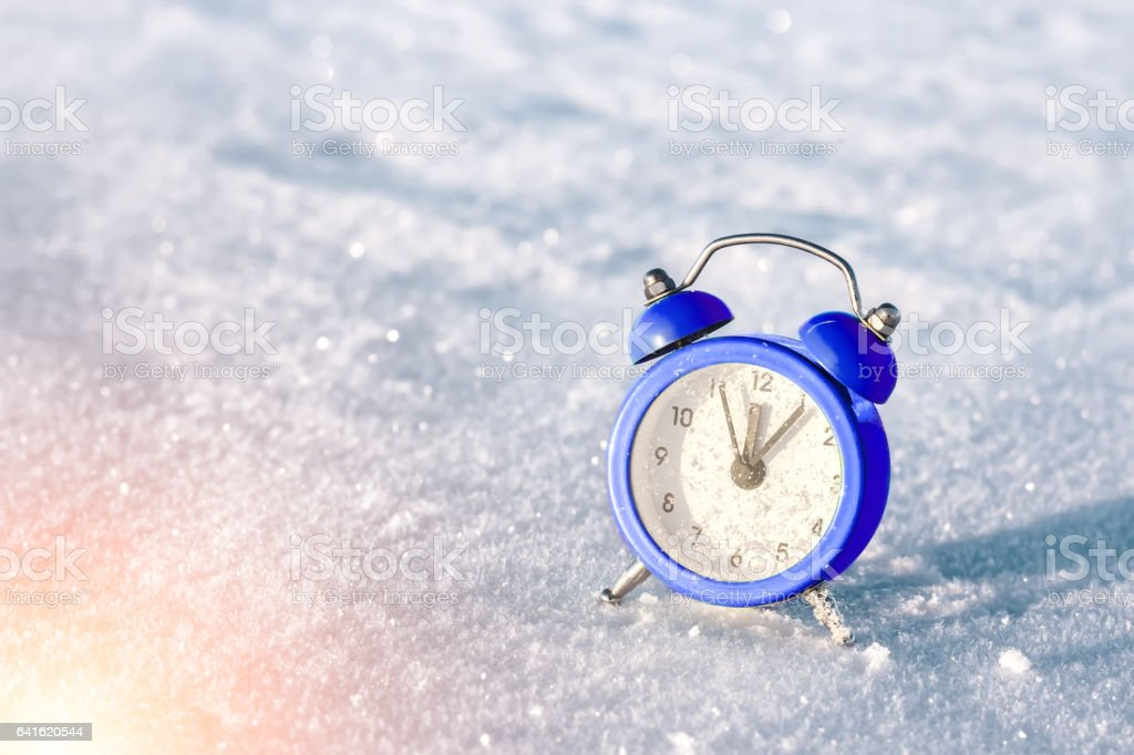 Vintage alarm clock on the snow at sunset. The concept of Christmas and New Year. Good morning. Waiting of holiday. stock photo