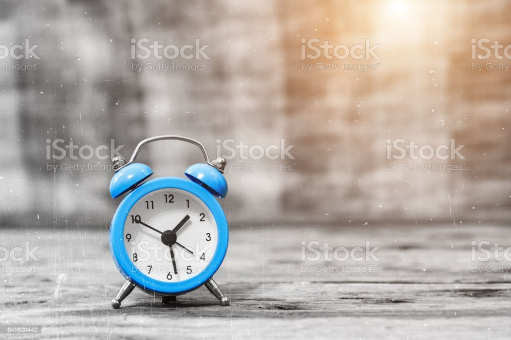 Vintage alarm clock on the wooden table stock photo