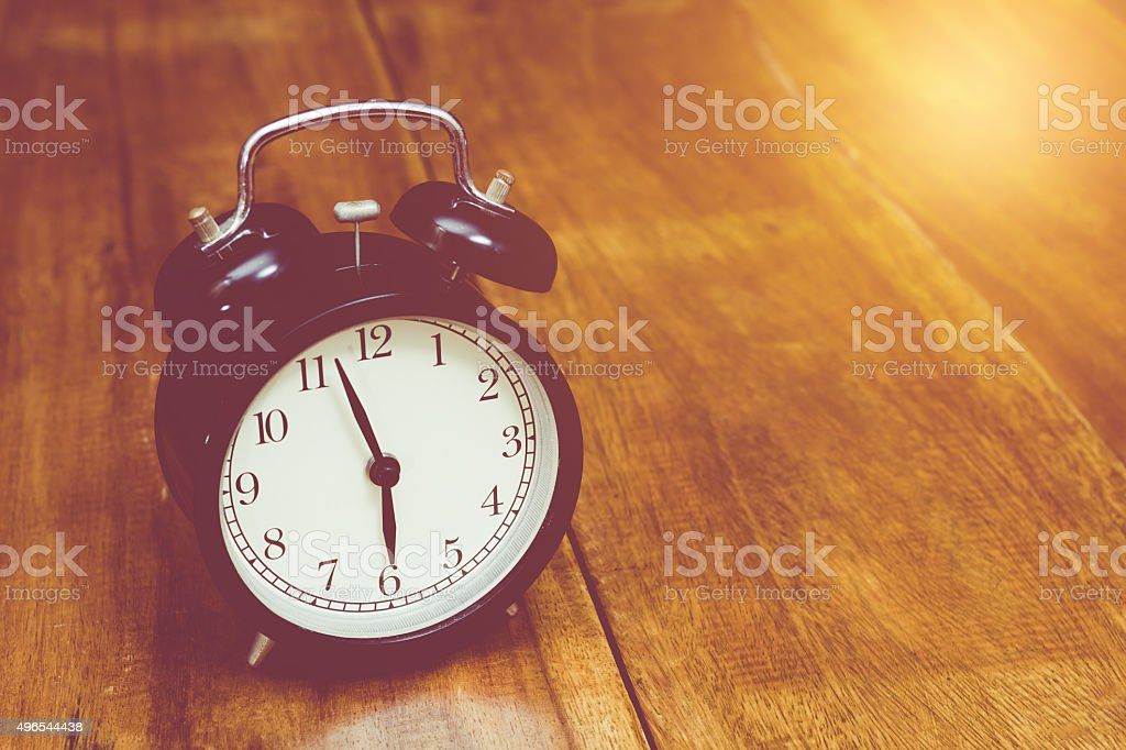 vintage alarm clock on wood stock photo