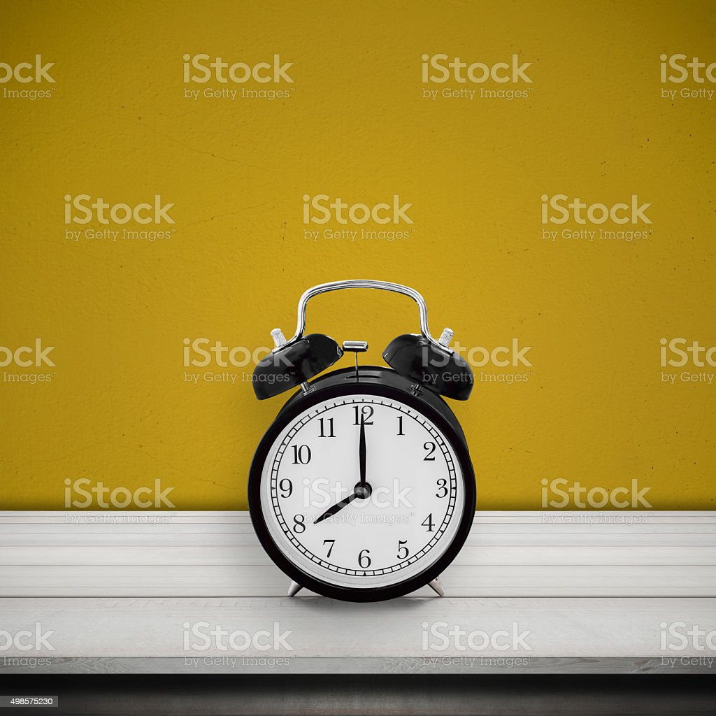 Vintage alarm clock on wood table desk over cement wall stock photo