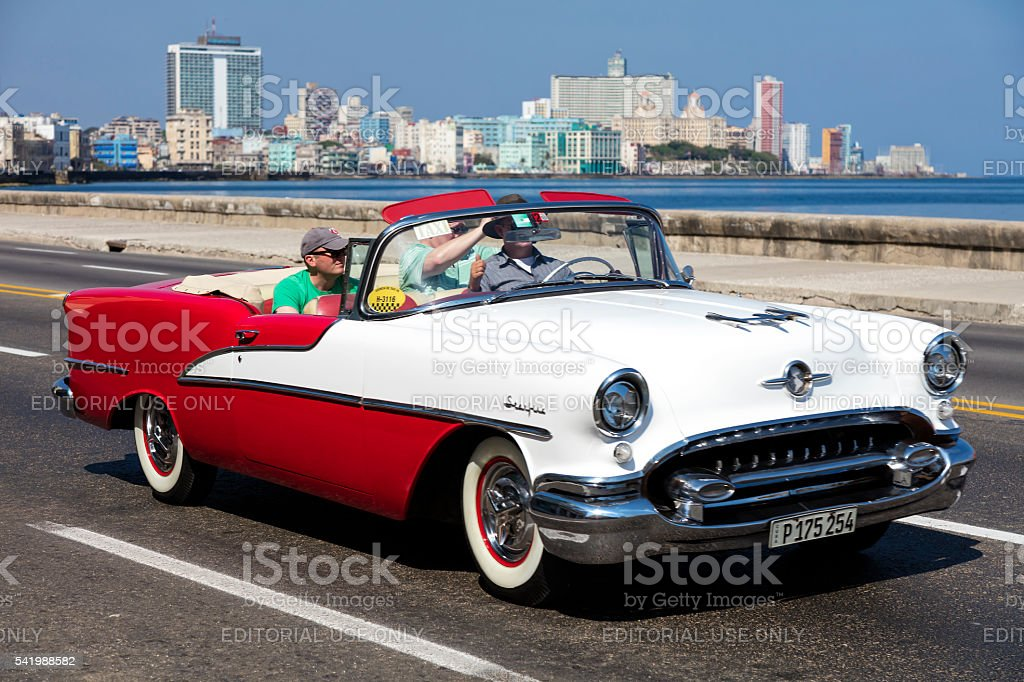 Vintage American car with tourists on Malecon, Havana, Cuba stock photo