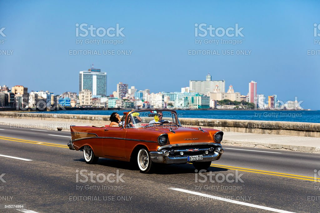 Vintage American car with tourists on Malecon, Havana, Cuba stock photo