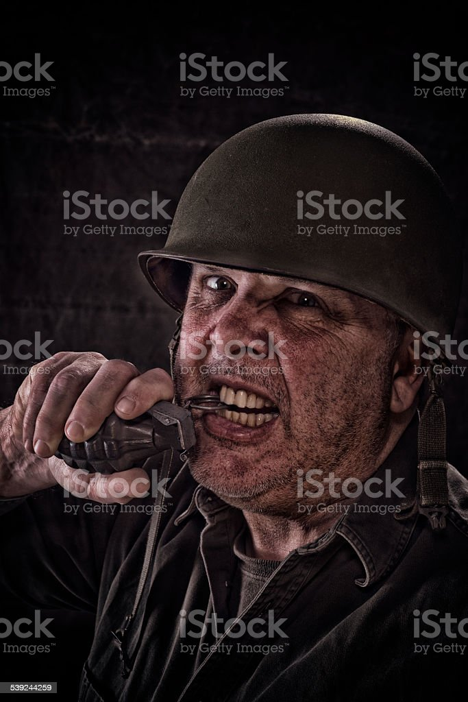 Vintage Army Soldier pulling pin on hand grenade with teeth stock photo