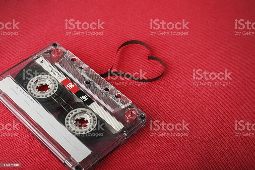 Vintage audio cassette with loose tape shaping a heart stock photo