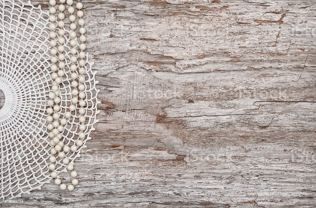 Vintage background with bead necklace and lace on old wood stock photo
