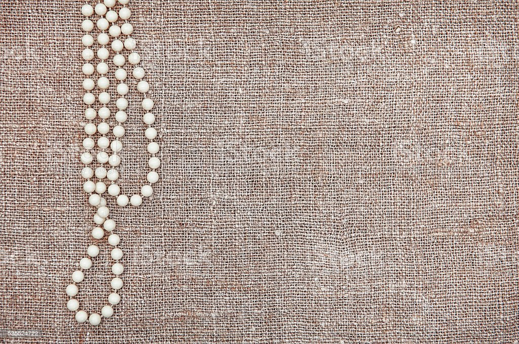 Vintage background with bead necklace on the old burlap stock photo