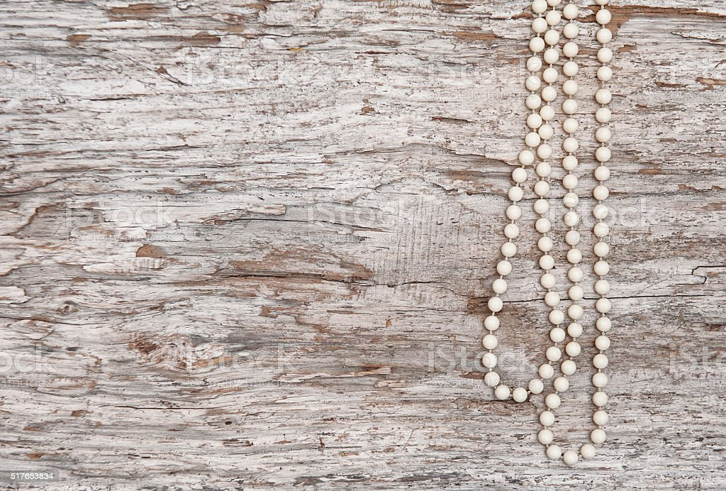 Vintage background with bead necklace on the old wood stock photo