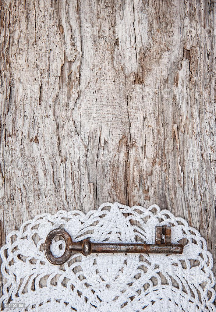 Vintage background with old key and lace on wood stock photo