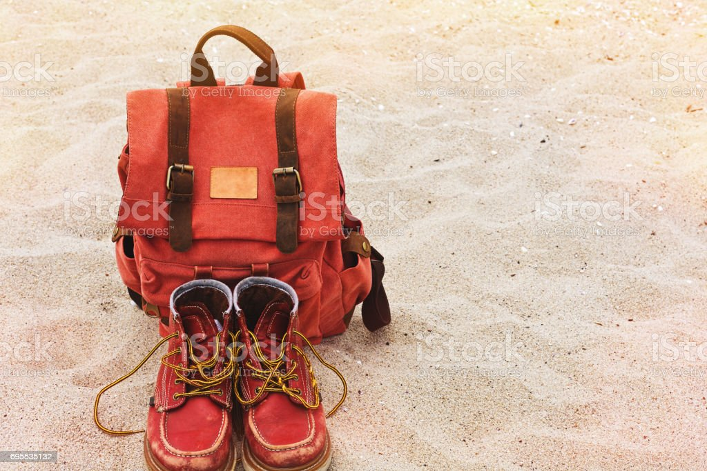 Vintage backpack and worn boots on the sand beach stock photo