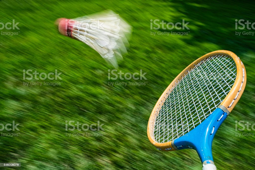 Vintage badminton racket hitting a shuttlecock in mid-air stock photo