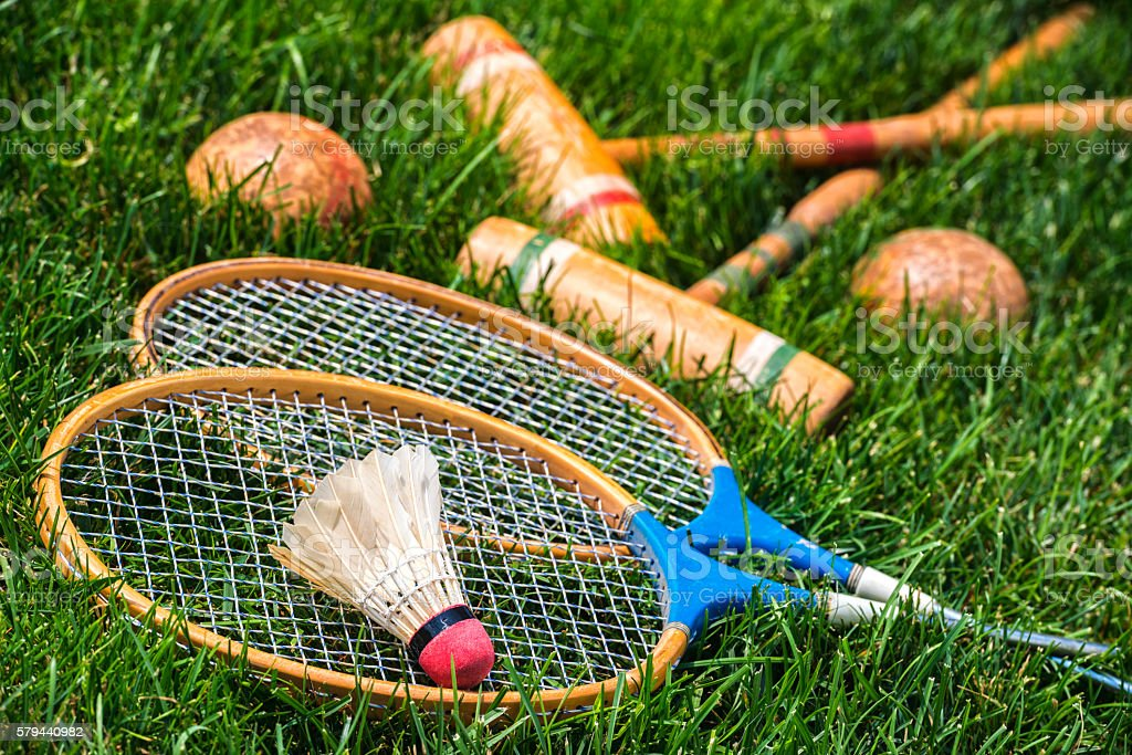 Vintage badminton rackets and croquet mallets lying in grass stock photo
