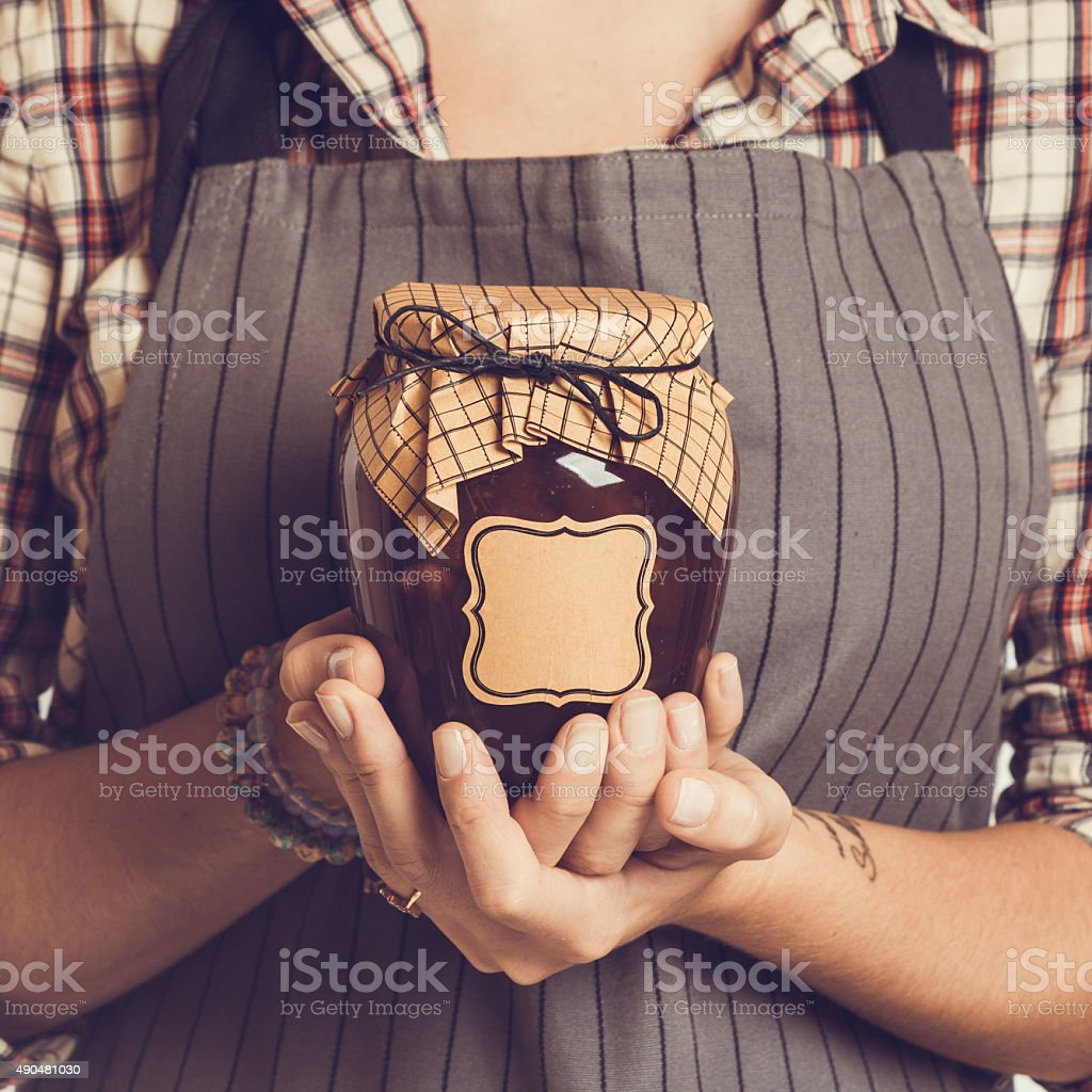 Vintage Bank peach jam in the hands of women. Close-up stock photo