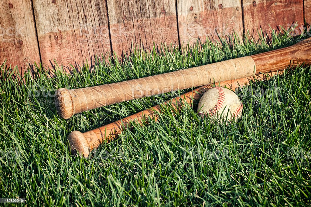 Vintage baseball and bats on grass near old wooden fence stock photo