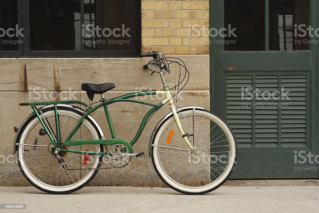 Vintage Bicycle Leaning Against Brick, Concrete Wall and Green Door royalty-free stock photo