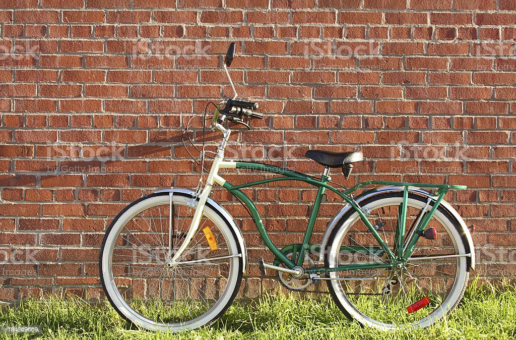 Vintage Bicycle Leaning Against Red Brick Wall In Summer royalty-free stock photo