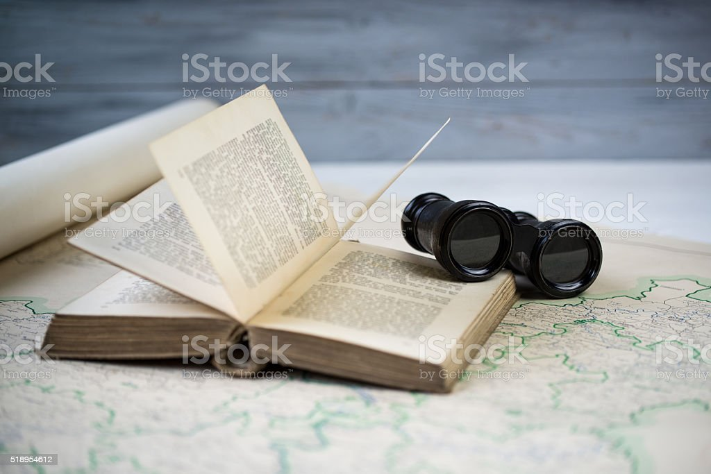 Vintage binoculars and antique opened book on the old map stock photo