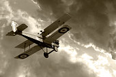 Vintage biplane flying into storm clouds