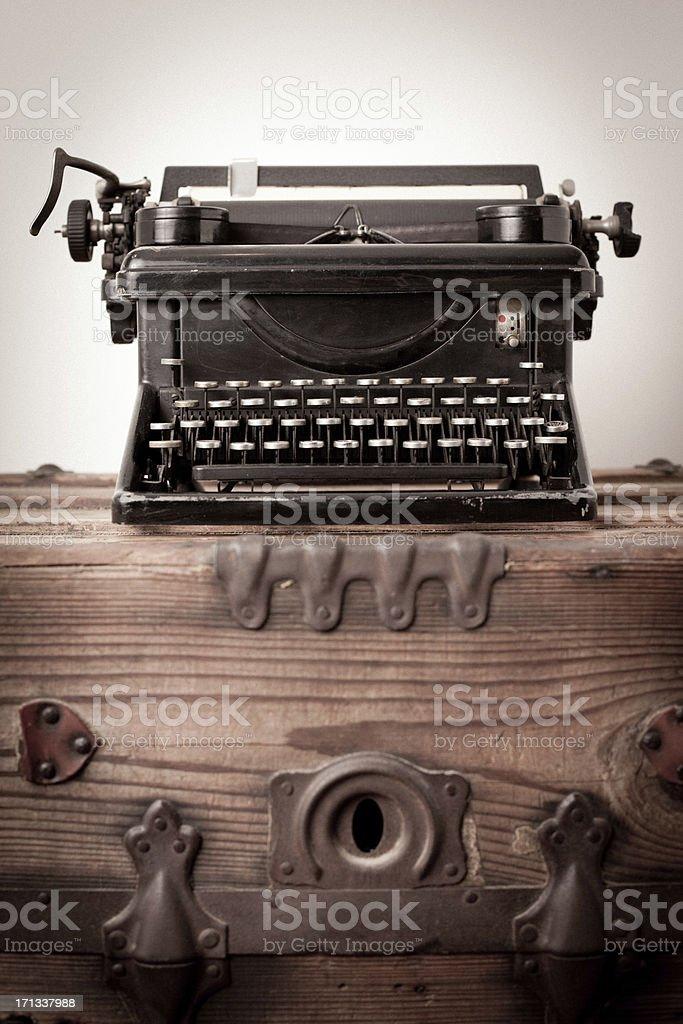 Vintage Black, Manual Typewriter, Sitting on Wood Trunk royalty-free stock photo