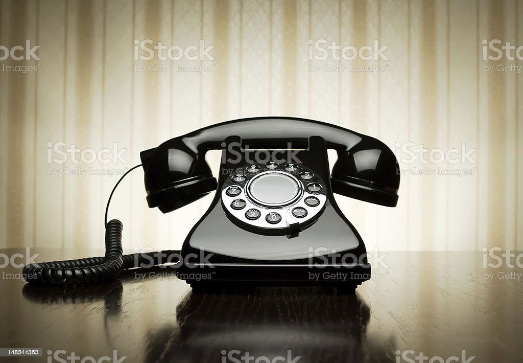 Vintage black rotary dial phone with striped wallpaper stock photo