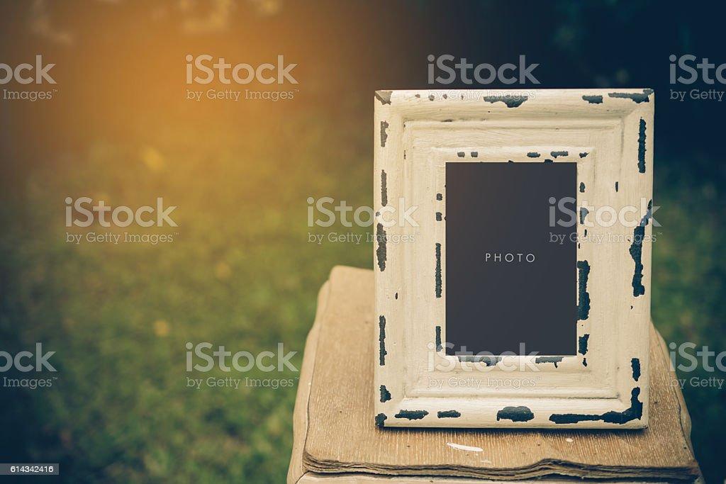 vintage blank frame on table in garden