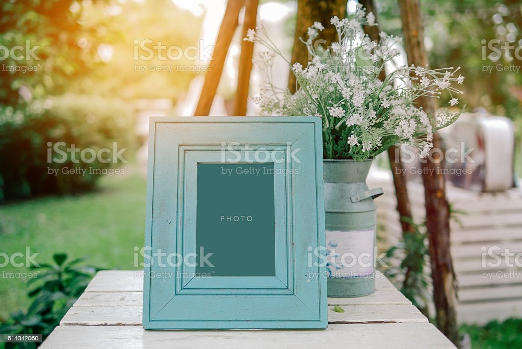 vintage blank frame with flowerpot on table in wedding day stock photo