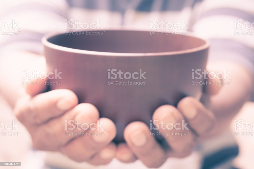 vintage blur of a hungry man holding an empty bowl stock photo