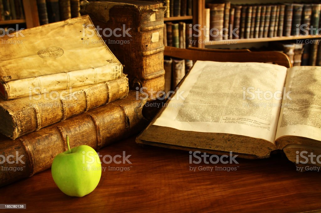 Vintage books in a library with an apple royalty-free stock photo