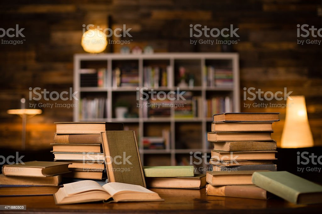 Vintage Books Sitting on Old Desk, With Shelved Wall Background royalty-free stock photo