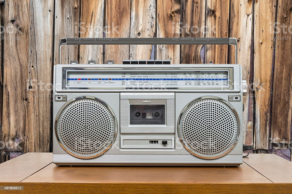 Vintage Boombox on Table with Rustic Cabin Wall stock photo
