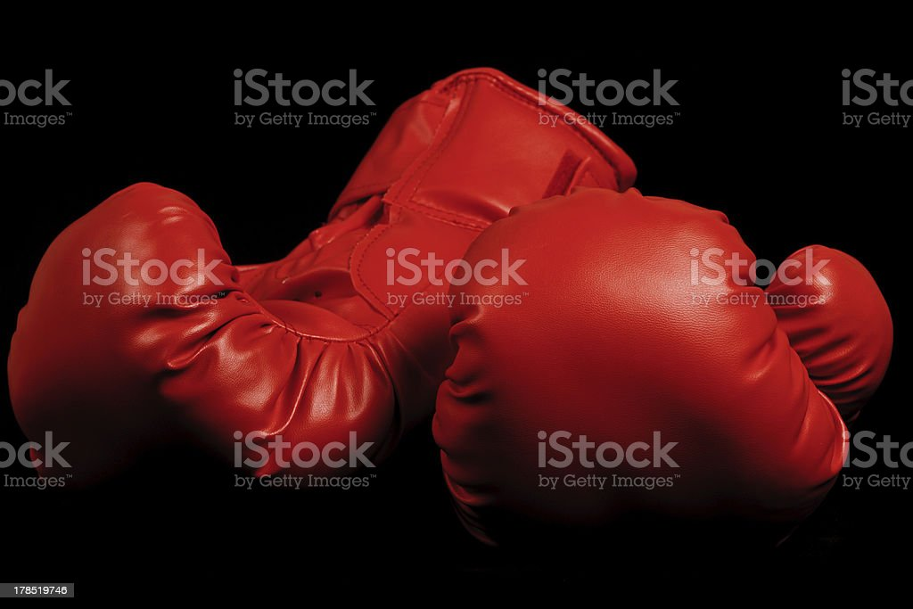 Vintage boxing gloves emerging from black background royalty-free stock photo