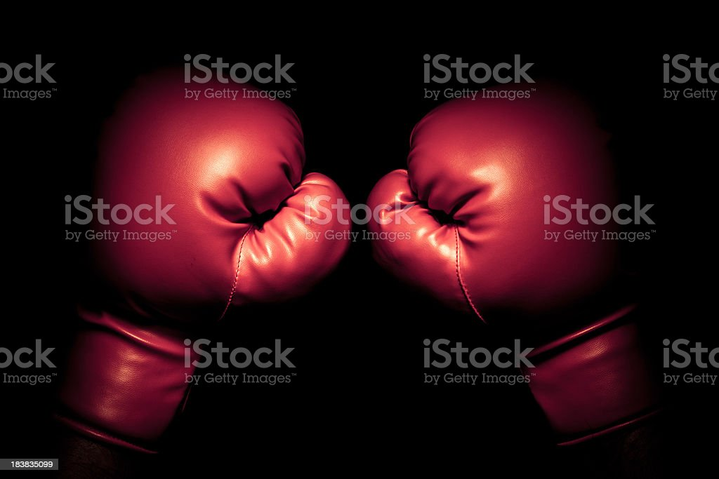 Vintage boxing gloves emerging from black background stock photo