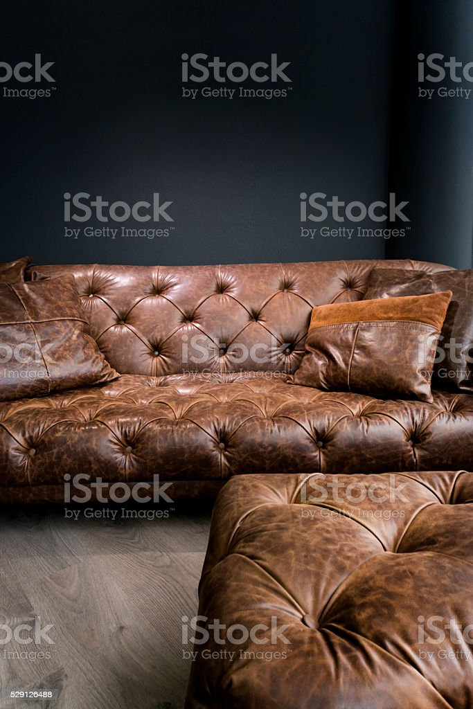 Vintage Brown Leather Sofa under Black Empty Wall stock photo