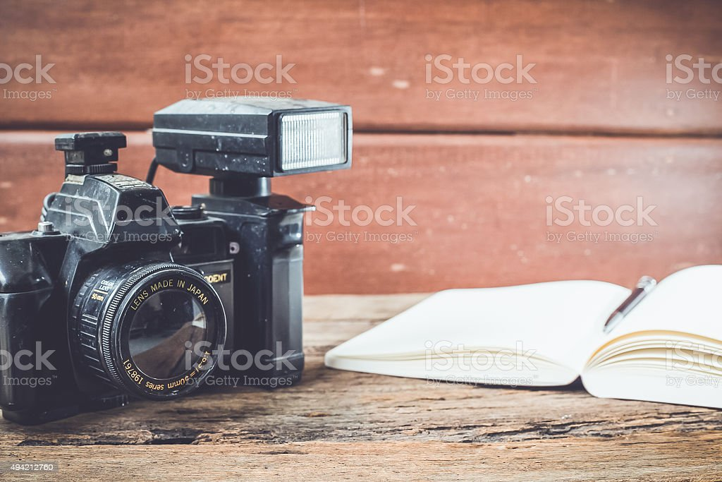 Vintage camera and book on wooden background stock photo