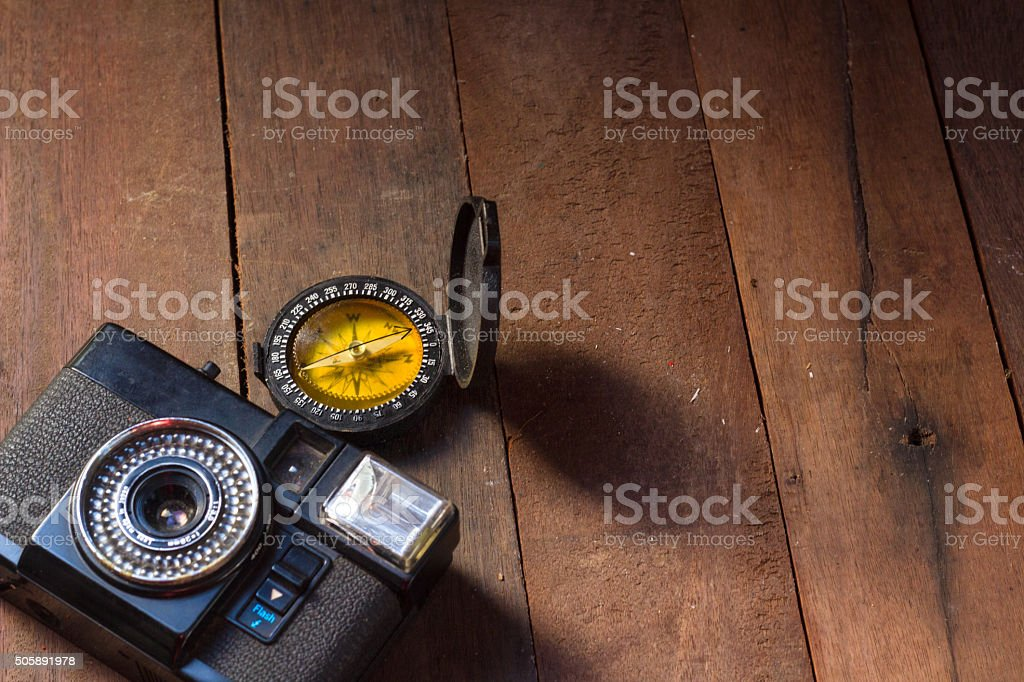 Vintage camera and compass  on wooden background stock photo