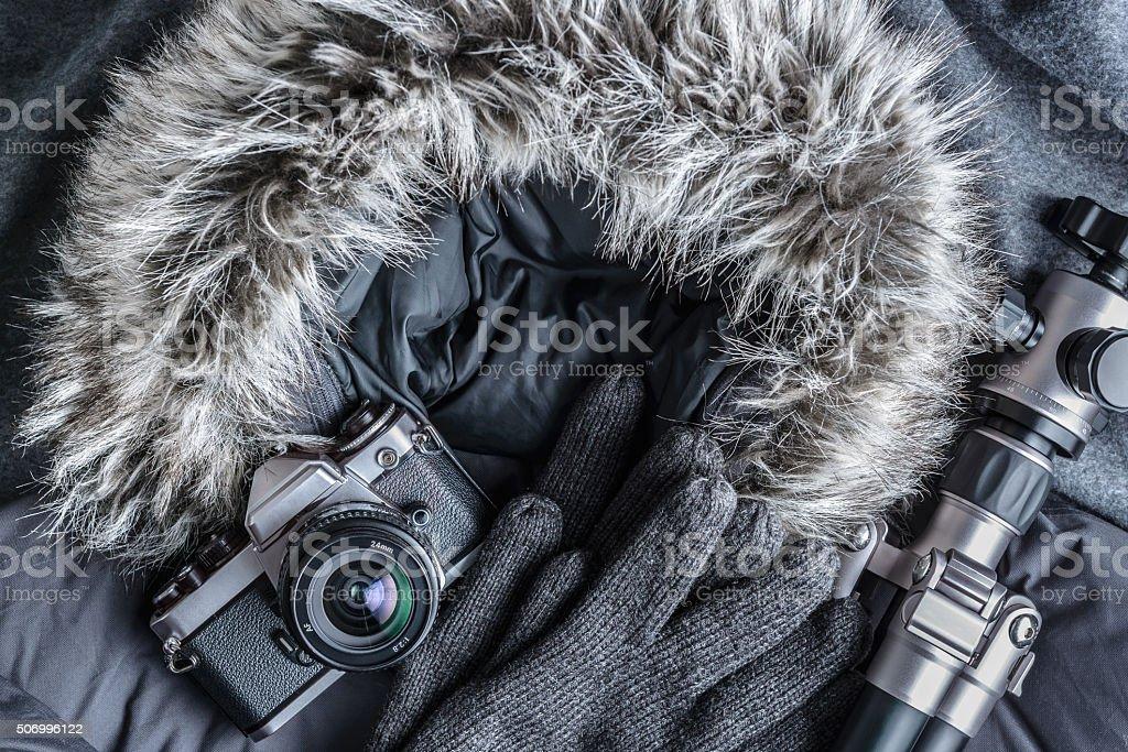 Vintage camera and tripod on fur hood coat. stock photo