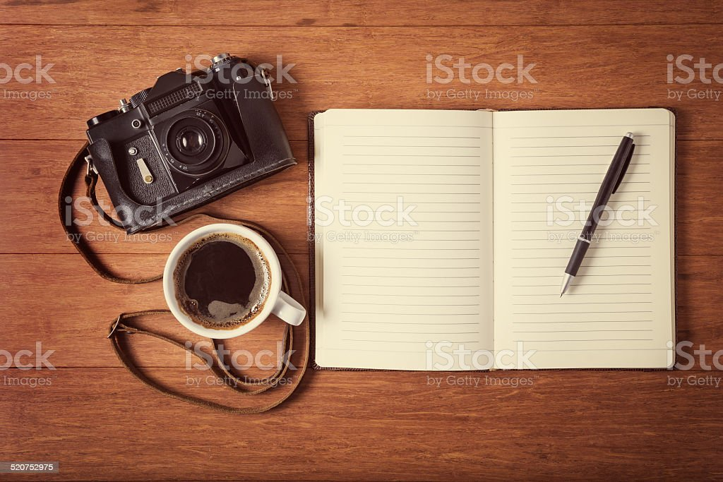 Vintage camera, diary and cup pf coffee on wooden table stock photo