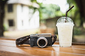 vintage camera with ice coffee on wooden table