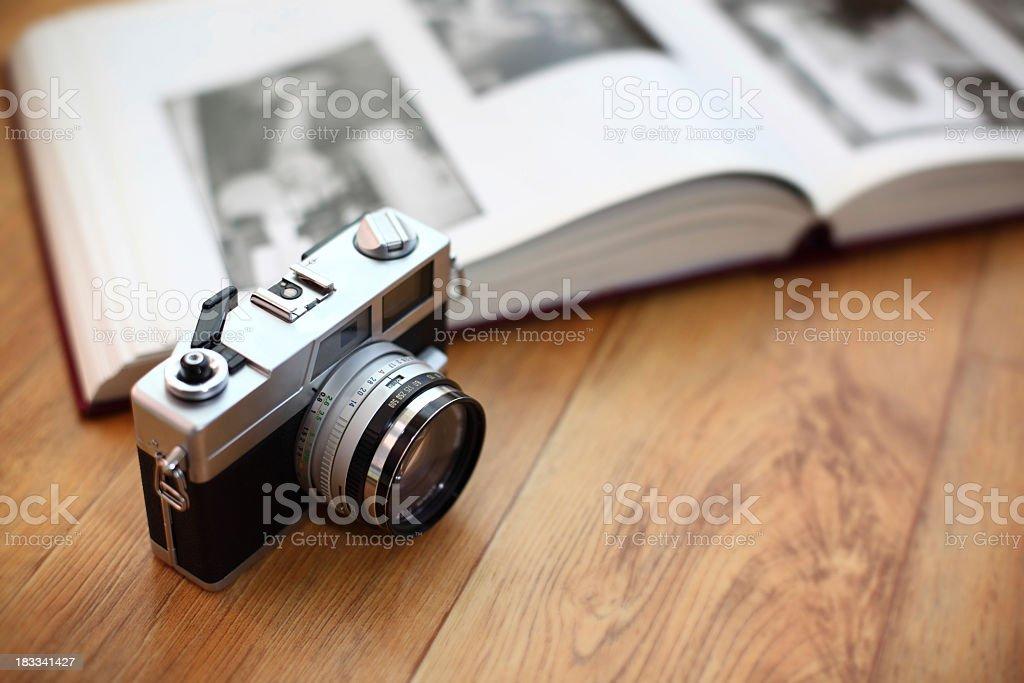 Vintage camera with photo album on wood surface stock photo