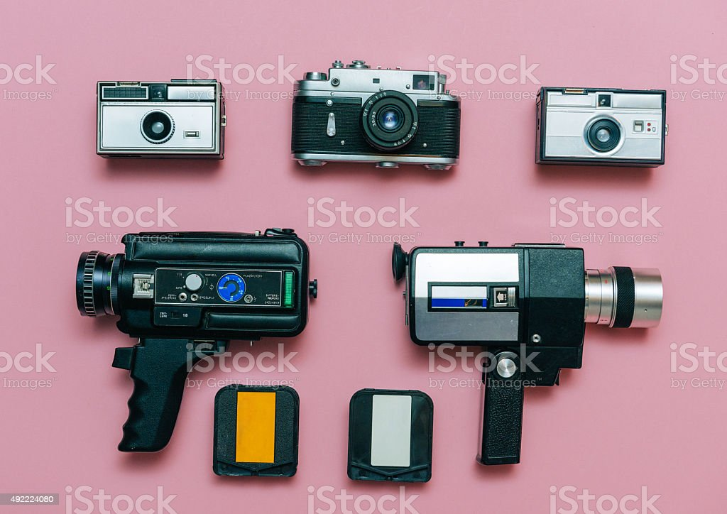 Vintage cameras and photo cameras with cassettes on pink background stock photo