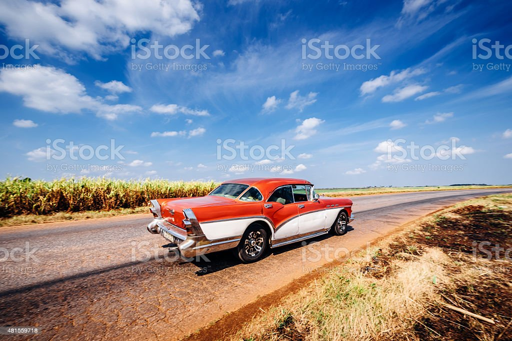Vintage car driving on rural road, Cuba stock photo