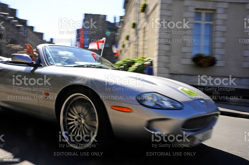 Vintage car rally, Brittany, France. A silver sports car with cross of St. George flag and hand throwing object. stock photo