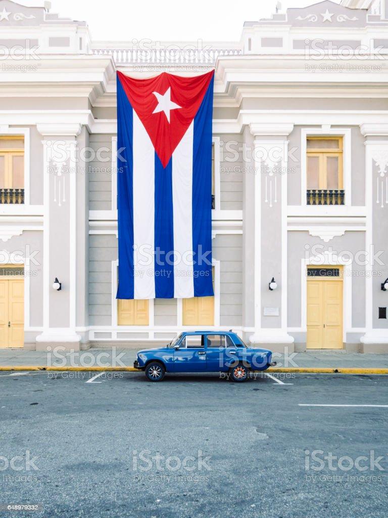 Vintage Car under a big Cuba flag in Cienfuegos stock photo