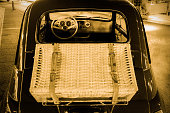 Vintage car with wicker suitcase