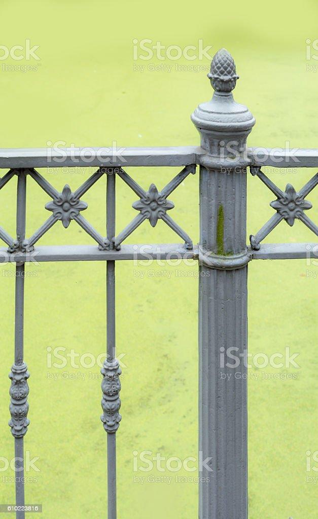 vintage cast iron bridge railing against duckweed backdrop stock photo