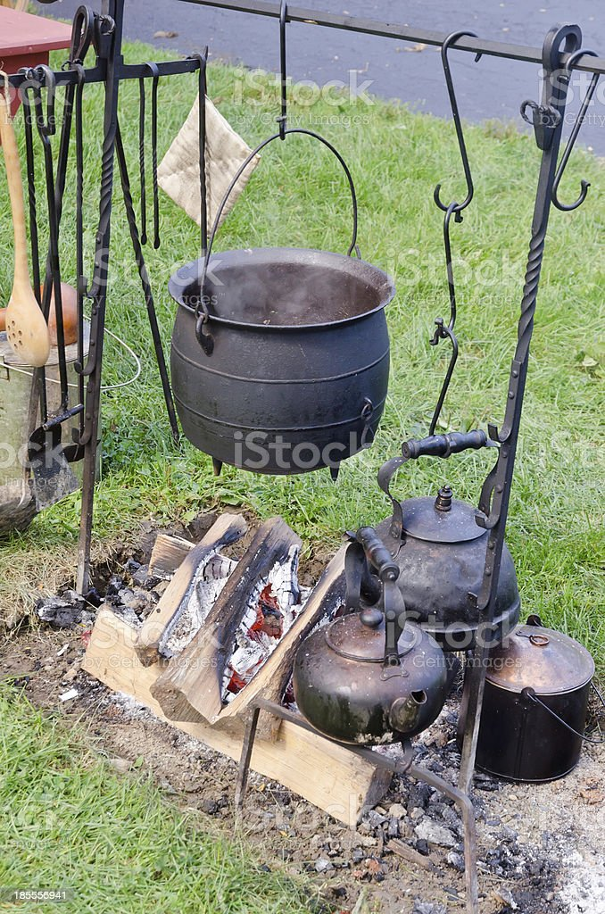 Vintage cast iron pot hanging over campfire royalty-free stock photo