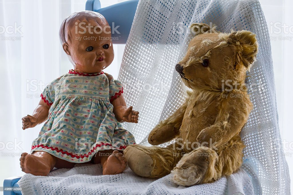Vintage ceramic doll and teddy bear sitting together on chair stock photo