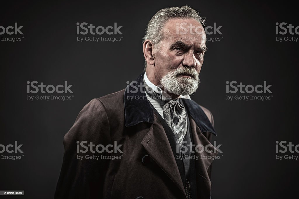 Vintage characteristic senior man with gray hair and beard. stock photo