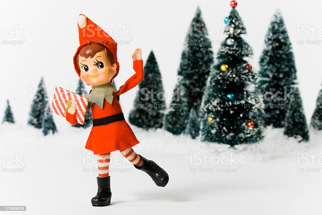 Vintage Christmas doll in front of Christmas trees stock photo