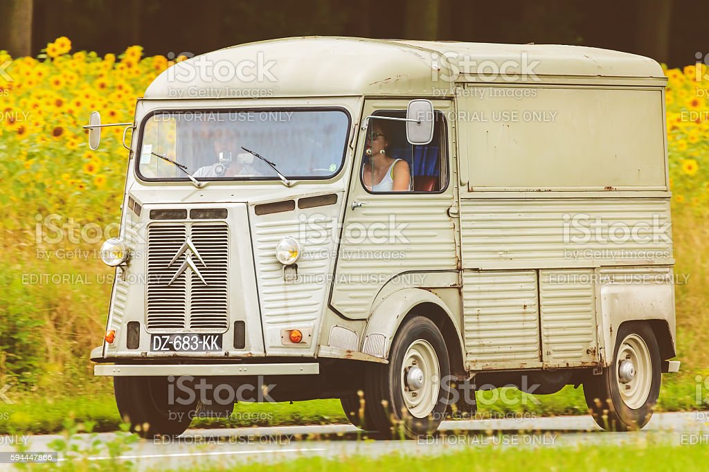 Vintage Citroen HY in front of a field with sunflowers stock photo