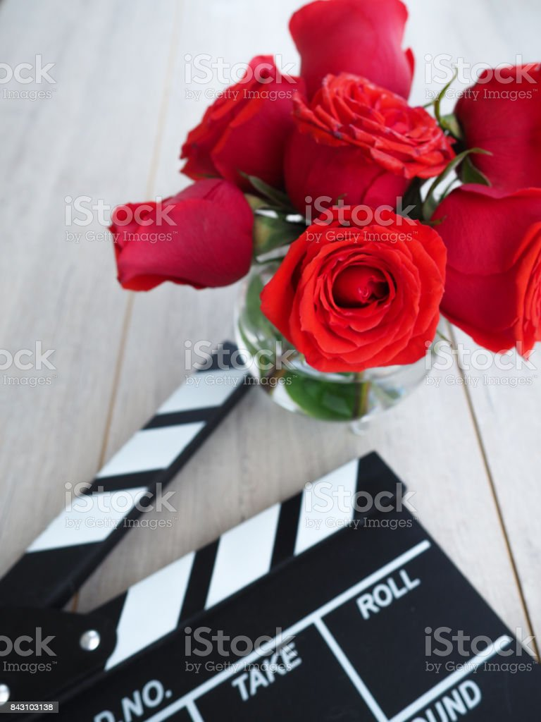 vintage classic clapperboard on brown wooden table whis red roses stock photo